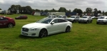 Jaguar XJ relaxs in the field next to the campsite. Row of Dacias behind, with a row of BMW M cars further back. Only at Goodwood.